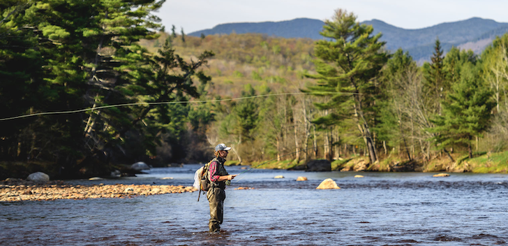 Person standing in river fly fishing with mountains in background