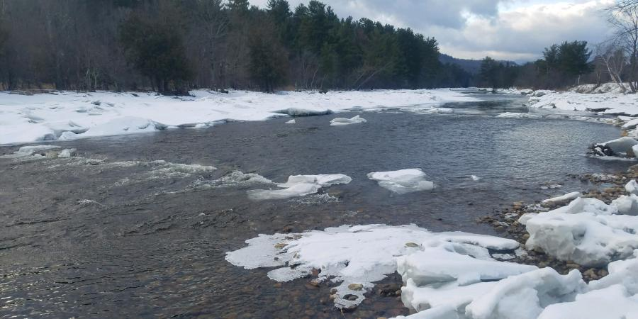 riffle on river with snow along banks