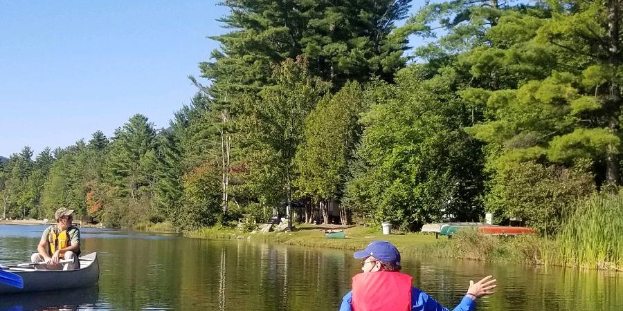 person in canoe educating other people in a canoe about invasive species on a pond