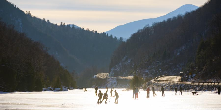 Group of people skating on a frozen lake with a country road and rolling mountains in the background