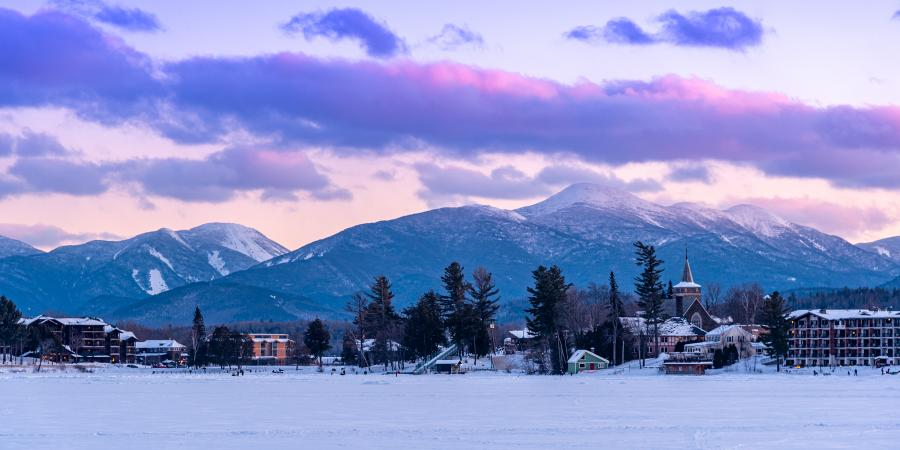 purple sunset over adirondack mountains taken from small lake with buildings around shore