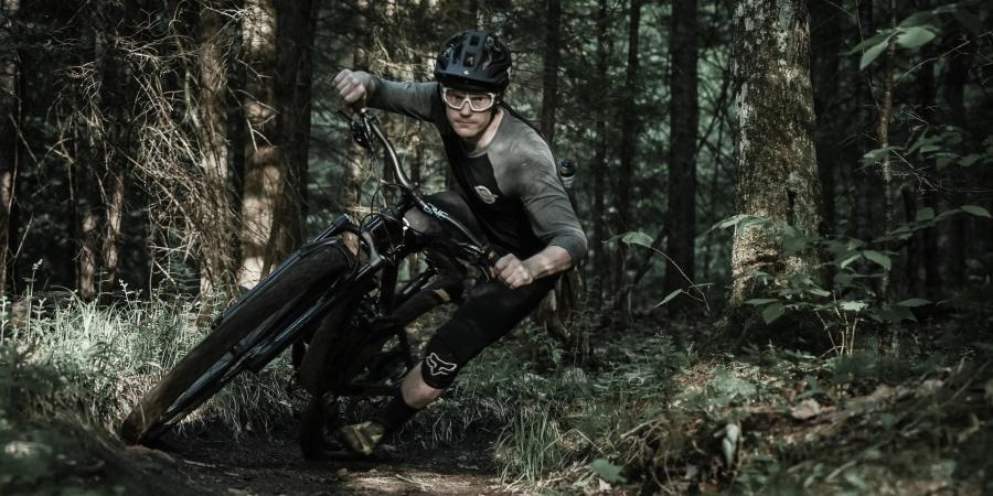 person mountain biking around a banked turn