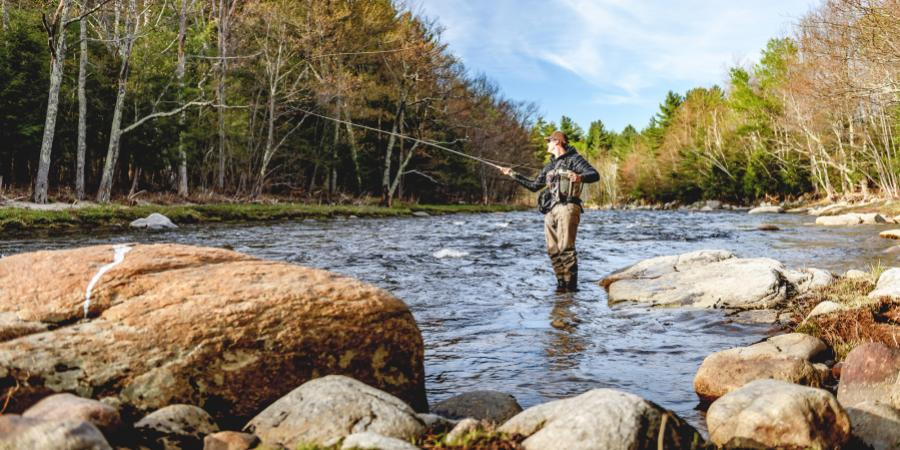 Man standing and fly fishing in middle of river during autumn