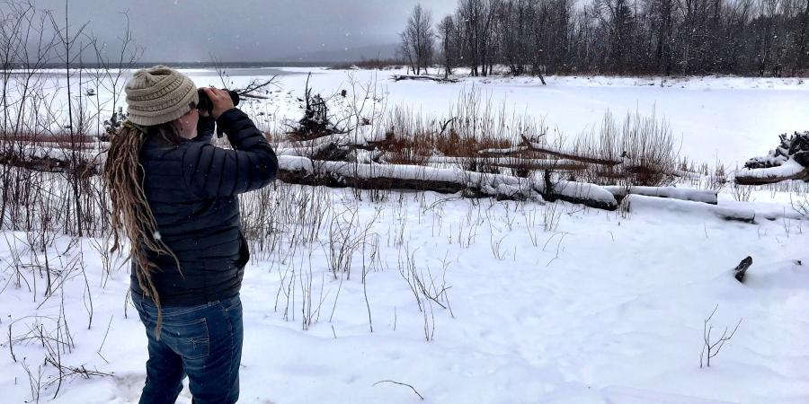 Woman using binoculars to view birds at snowy lake in winter