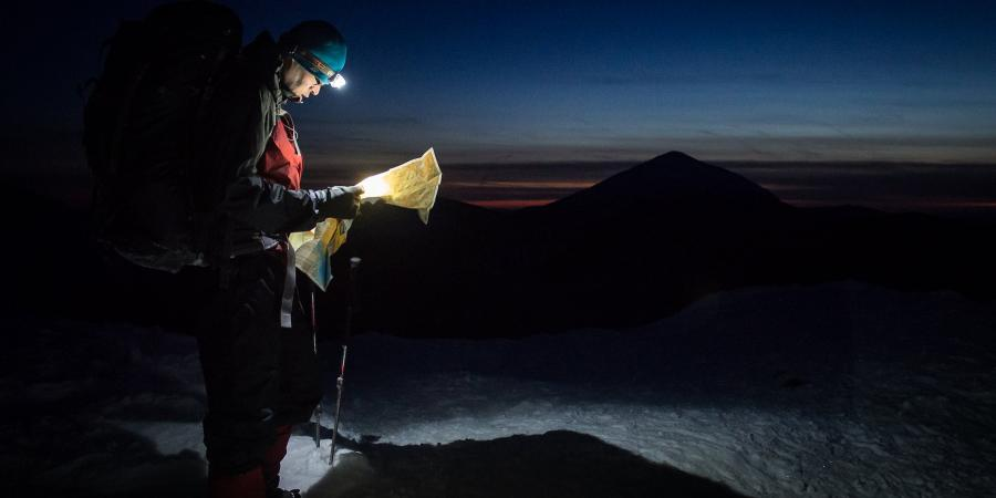 Winter hiker on the summit of a mountain looking at a map by headlamp